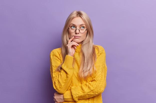 Jeune jolie jeune femme pense à des idées concentrées au-dessus se tient pensif et garde la main sur le visage se dresse dans une pose réfléchie porte des lunettes rondes chandail jaune