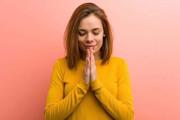 Jeune et jolie jeune femme se tenant la main dans la prière près de la bouche, se sent confiante.
