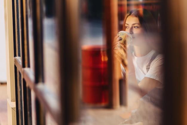 Jeune jolie jolie fille au café avec café se détendre au verre du matin throuth