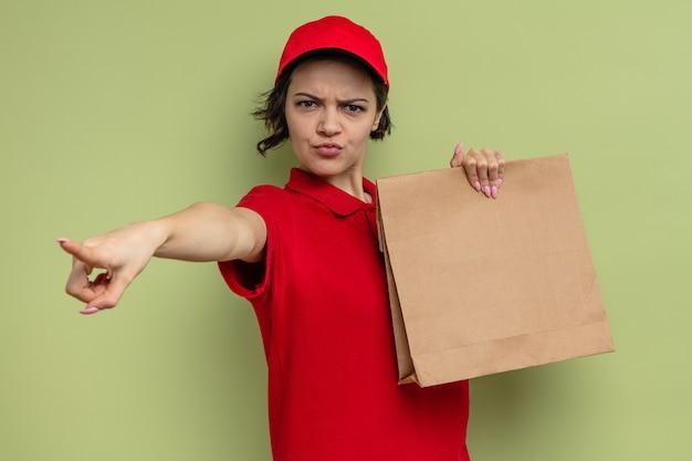 Jeune jolie livreuse agacée tenant un sac de nourriture en papier et pointant sur le côté