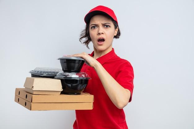 Jeune jolie livreuse choquée tenant des contenants de nourriture et des emballages sur des boîtes à pizza