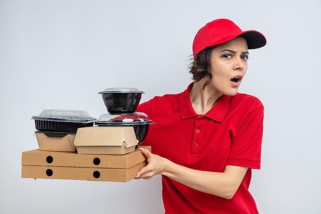 Jeune jolie livreuse ignorante tenant des contenants de nourriture et des emballages sur des boîtes à pizza