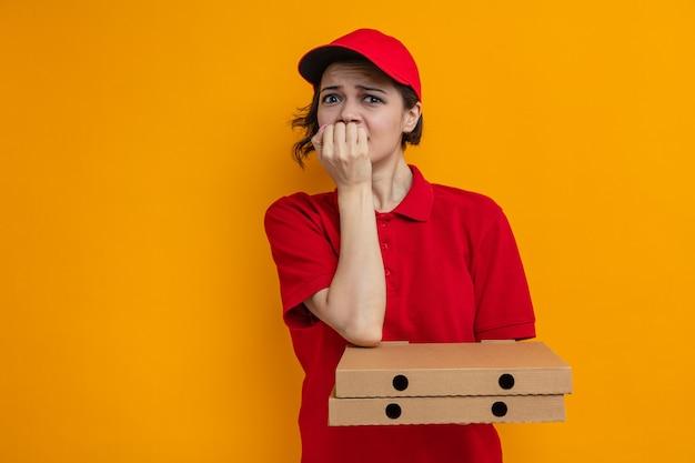 Jeune jolie livreuse inquiète tenant des boîtes à pizza et se rongeant les ongles