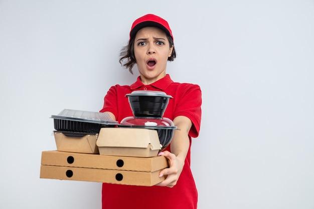 Jeune jolie livreuse inquiète tenant des contenants de nourriture et des emballages sur des boîtes à pizza
