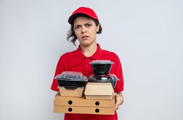 Jeune jolie livreuse mécontente tenant des contenants de nourriture et des emballages sur des boîtes à pizza