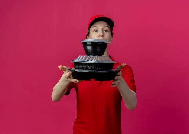 Jeune jolie livreuse portant l'uniforme rouge et une casquette regardant la caméra étirant les contenants de nourriture à la caméra isolée sur fond cramoisi avec espace copie