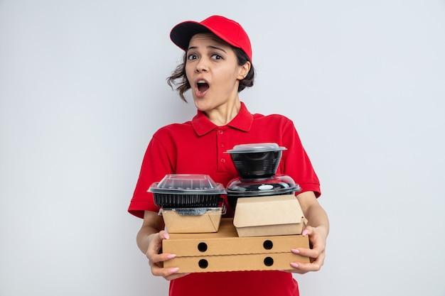 Jeune jolie livreuse surprise tenant des contenants de nourriture et des emballages sur des boîtes à pizza