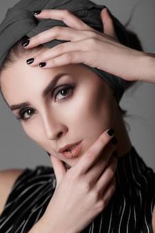 Jeune jolie mannequin avec un châle gris sur la tête