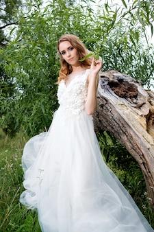 Jeune jolie mariée en robe de mariée blanche à l'extérieur