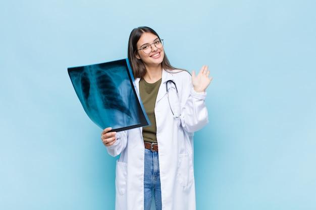 Jeune jolie médecin souriant joyeusement et gaiement, agitant la main, vous accueillant et vous saluant, ou vous disant au revoir