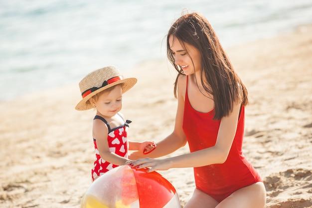 Jeune jolie mère jouant avec sa petite fille mignonne à la plage. maman aimante s'amuser avec son enfant au bord de la mer