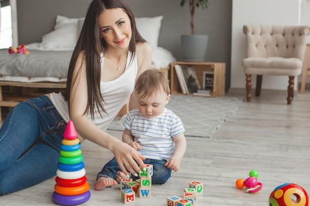 Jeune jolie mère jouant avec son petit fils. famille joyeuse s'amuser à l'intérieur avec petit bébé
