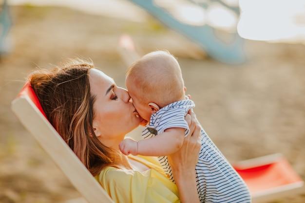 Jeune jolie mère en robe de plage d'été jaune portant sur une chaise de plage rouge embrassant son nouveau-né.