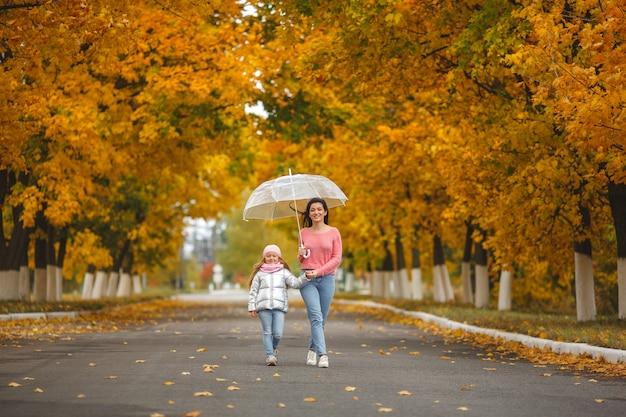 Jeune jolie mère avec sa petite fille s'amusant. héhé en automne
