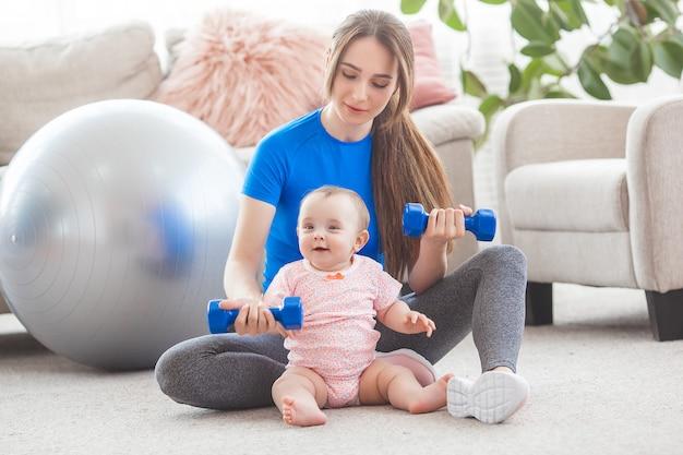 Jeune jolie mère travaillant avec son petit enfant à la maison