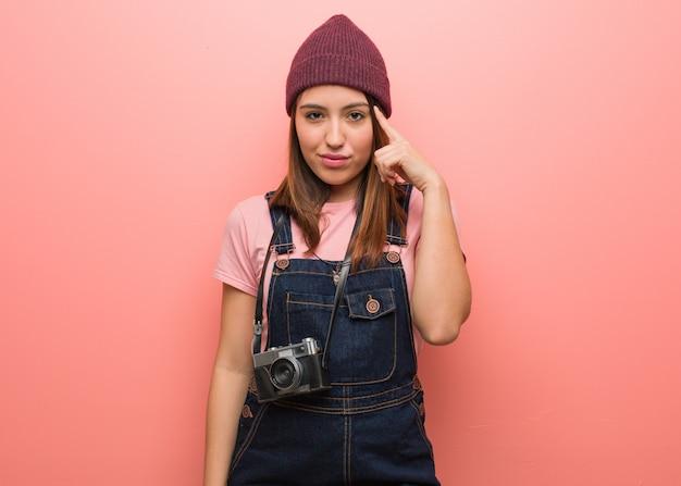 Jeune jolie photographe femme réfléchissant à une idée
