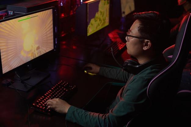 Jeune joueur asiatique à lunettes à l'écran de l'ordinateur, il se concentre sur son jeu dans un club informatique sombre