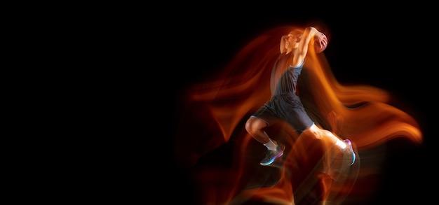 Jeune joueur de basket-ball d'asie de l'est en action et saut dans une lumière mixte sur fond de studio sombre