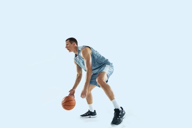 Jeune joueur de basket-ball caucasien contre fond blanc studio