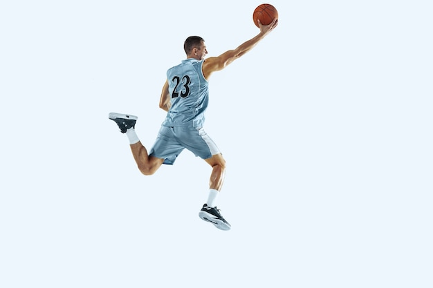 Jeune joueur de basket-ball caucasien de haut vol de l'équipe en mouvement d'action en saut isolé