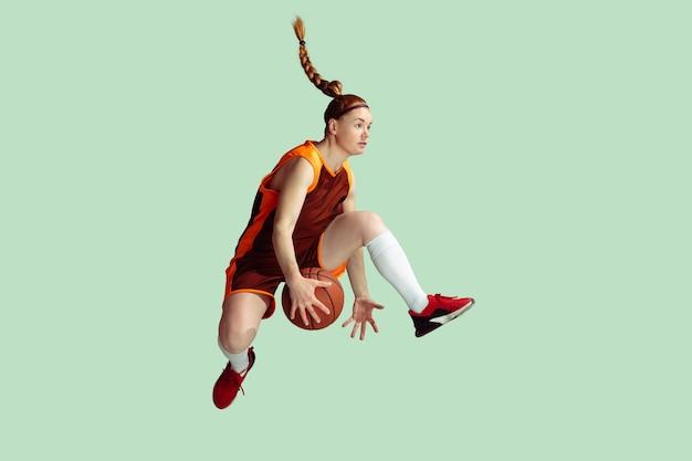 Jeune joueur de basket-ball féminin caucasien en action, mouvement en saut en hauteur isolé sur fond de couleur menthe. concept de sport, mouvement, énergie et mode de vie sain et dynamique. entraînement, pratique.