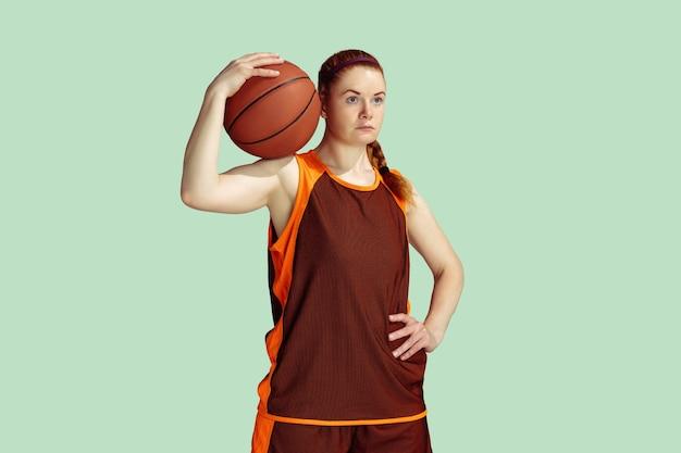 Jeune joueur de basket-ball féminin caucasien confiant tenant le ballon posant isolé