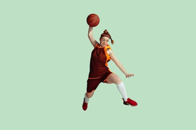 Jeune joueur de basket-ball féminin caucasien en mouvement d'action en saut en hauteur isolé sur menthe