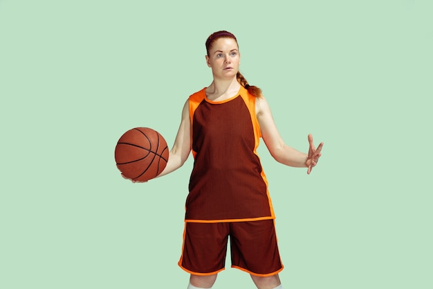 Jeune joueur de basket-ball féminin de race blanche sur fond de studio de couleur menthe