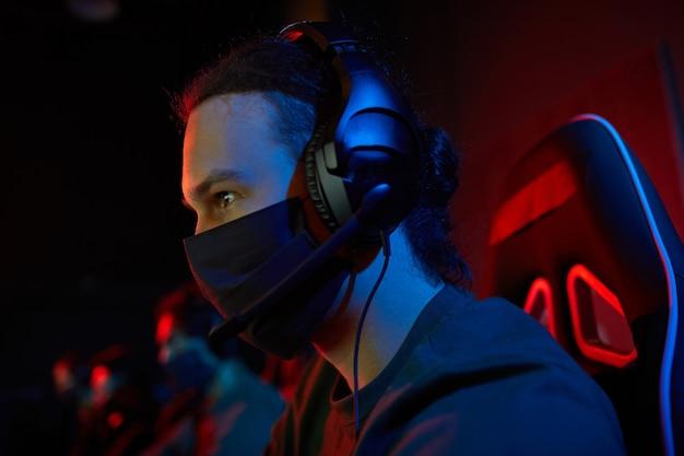 Jeune joueur dans les écouteurs et dans un masque de protection jouant à des jeux informatiques dans une pièce sombre