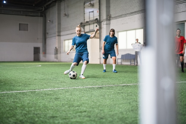 Jeune joueur de football actif en uniforme de sport bleu va botter le ballon de football tout en le suivant sur champ vert pendant le match