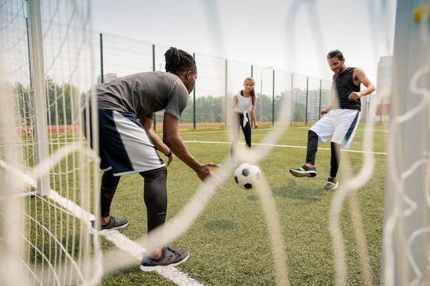 Jeune joueur de football africain attraper le ballon pendant que son rival le frappe pendant le match sur le terrain