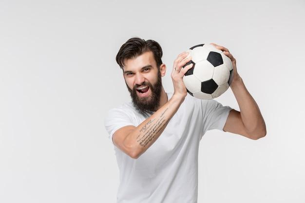 Jeune joueur de football avec ballon devant le mur blanc