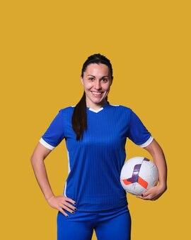 Jeune joueur de football féminin avec un ballon sur un mur isolé jaune