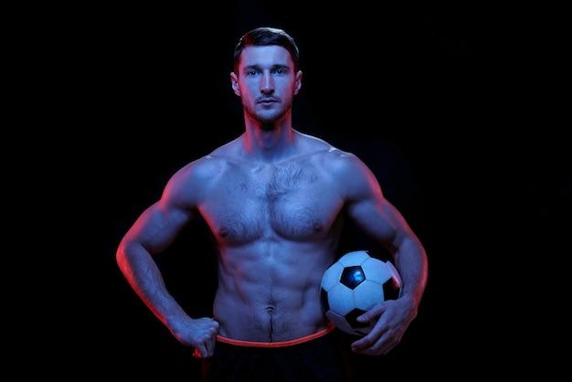 Jeune joueur de football torse nu musclé sérieux avec ballon de foot debout devant la caméra sur fond noir en isolement