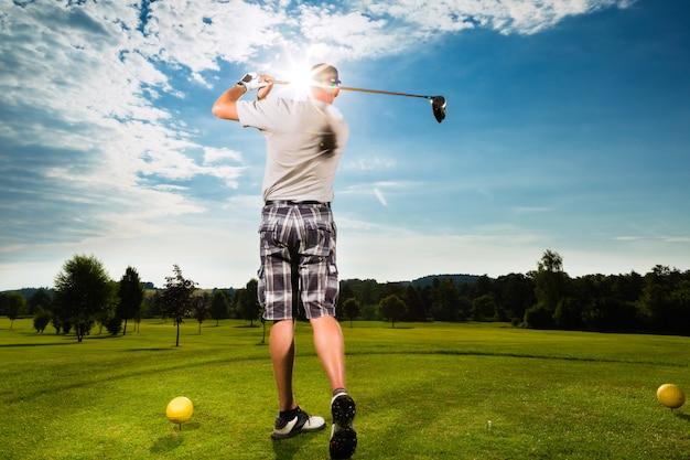 Jeune joueur de golf sur le parcours de golf swing