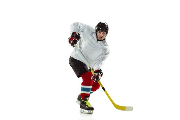 Jeune Joueur De Hockey Masculin Avec Le Bâton Sur Le Court De Glace Et Fond Blanc. Photo gratuit