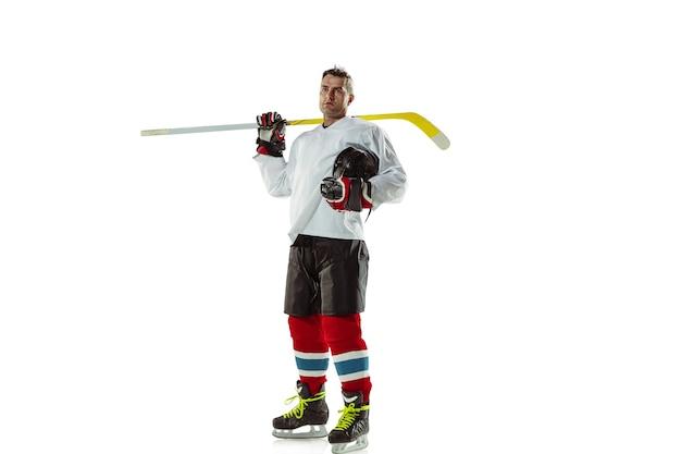 Jeune joueur de hockey masculin avec le bâton sur un court de glace et un mur blanc
