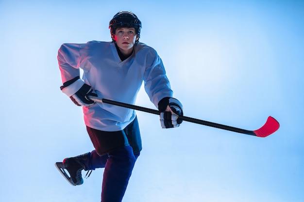 Jeune joueur de hockey masculin avec le bâton sur un mur blanc en néon