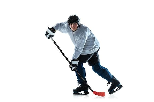 Jeune joueur de hockey masculin sérieux avec le bâton sur la cour de glace et le mur blanc