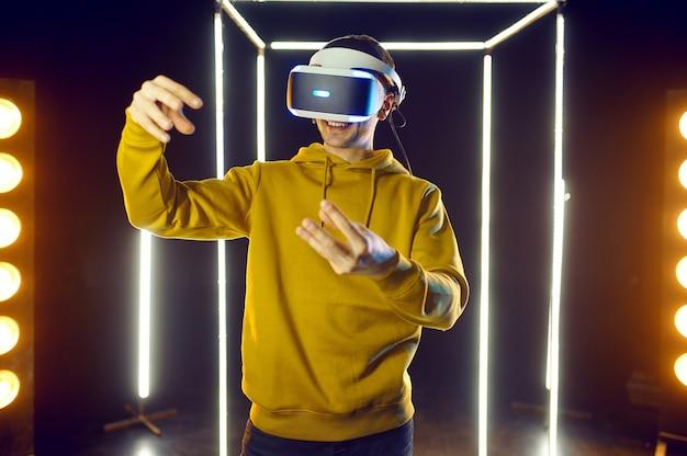 Jeune joueur joue au jeu de simulation dans un casque de réalité virtuelle et une manette de jeu dans un cube lumineux, vue de face