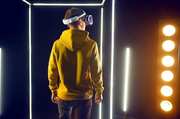 Le jeune joueur joue au jeu en utilisant un casque de réalité virtuelle et une manette de jeu dans un cube lumineux. intérieur du club de jeu sombre, technologie vr avec vision 3d