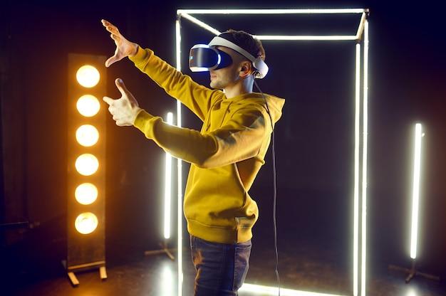 Le jeune joueur joue au jeu en utilisant un casque de réalité virtuelle et une manette de jeu dans un cube lumineux, vue de face. intérieur du club de jeu sombre, technologie vr avec vision 3d