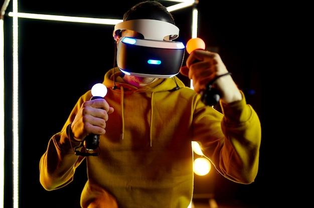 Jeune joueur joue dans un casque de réalité virtuelle et une manette de jeu dans un cube lumineux, vue de face. intérieur du club de jeu sombre, technologie vr avec vision 3d