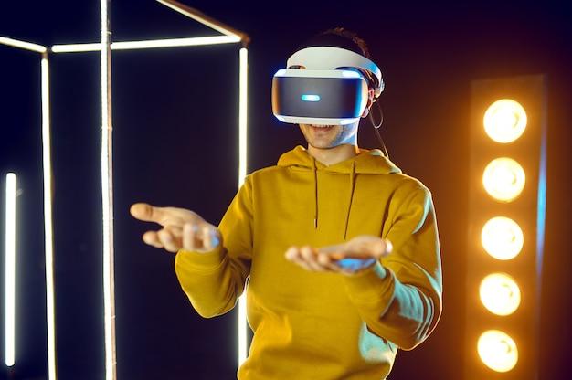 Le jeune joueur joue à un jeu de simulation dans un casque de réalité virtuelle et une manette de jeu dans un cube lumineux, vue de face. intérieur sombre du club de jeu, projecteur sur l'arrière-plan, technologie vr, vision 3d