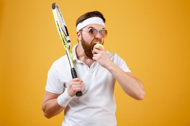 Jeune joueur de tennis affamé mord la balle de tennis.