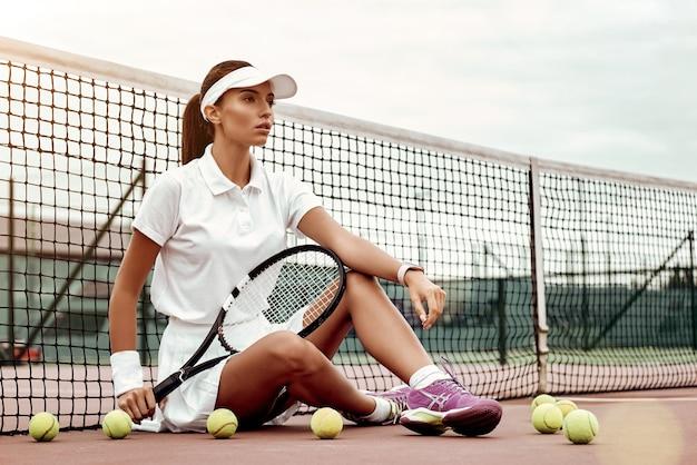 Jeune joueur de tennis assis sur un court et tenant une raquette