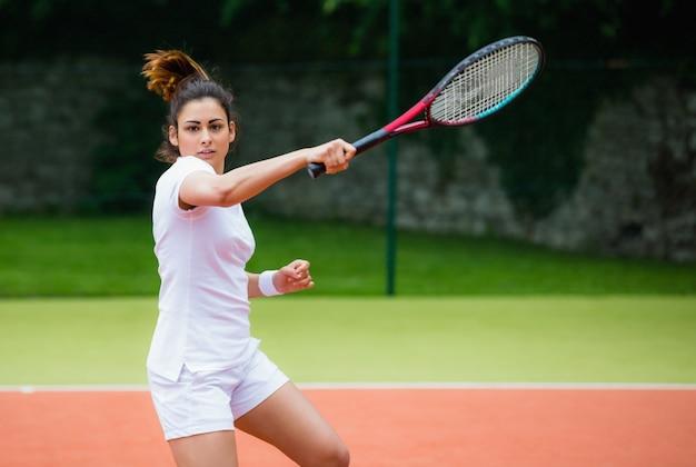 Jeune joueur de tennis frapper la balle