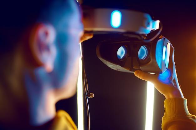 Le jeune joueur tient un casque de réalité virtuelle et une manette de jeu dans un cube lumineux. intérieur du club de jeu sombre, technologie vr avec vision 3d