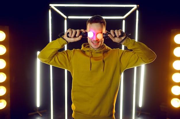 Jeune joueur tient des manettes de jeu de réalité virtuelle à ses yeux dans un cube lumineux, vue de face