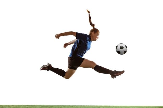 Jeune joueuse de football ou de football aux cheveux longs frappant le ballon pour le but en vol, sautant haut sur fond de studio blanc. concept de mode de vie sain, sport professionnel, mouvement, mouvement.
